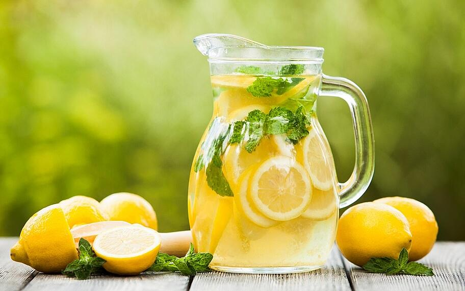 A jug of lemonade with lemons surround it on the table
